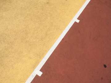 Lignes de terrain de basket - sol en béton rouge et jaune.