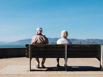 Sunday Strolls - man and woman sitting on bench facing sea. Lands End, San Francisco, United States