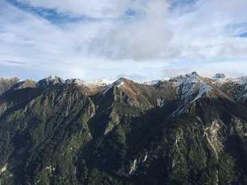 Góry Nowej Zelandii - góry z drzewami pod chmurnym niebem. Nowa Zelandia