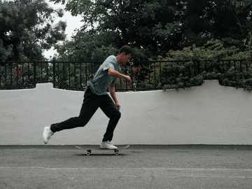 Skateboarding derribado - el hombre viste una camiseta verde y un pantalón negro con fotografía de primer plano.