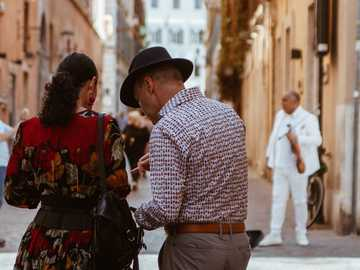 man in white and gray dress shirt beside woman in red, orange, and gray floral dress standing outside house - This is a couple understanding where to go in Rome. She has a beautiful flower dress, he wears a vin