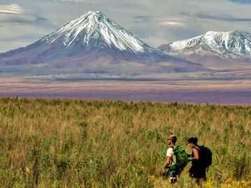 mężczyzna i kobieta siedzi na polu trawy w pobliżu góry w ciągu dnia - Backpacking w Andach Młoda para, ciesząca się wolnością, przestrzenią i pięknem Andów. El Lo