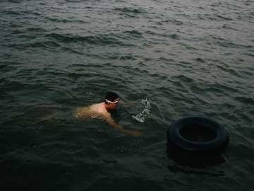 Swimming is of lots of fun - man swimming near black life ring. 中国武汉市武昌区东湖南路凌波门