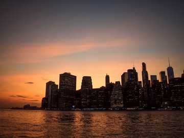 New York City at sunset - silhouette of high-rise building beside sea during golden hour. New York City, État de New York, É
