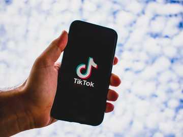 personne, tenue, noir, iphone 5 - iPhone affichant l'application TikTok.
