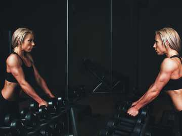 Strength training - woman wearing black top top holding black dumbbells standing in front of mirror.