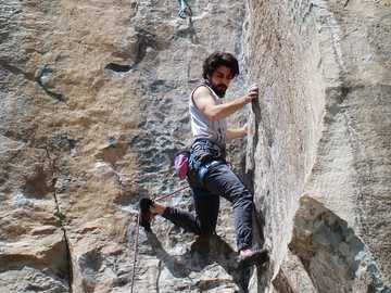 H route (5.11bc) Sina Navidi - woman in white tank top and blue denim jeans climbing on brown rock during daytime. Pol-e Khab, Albo