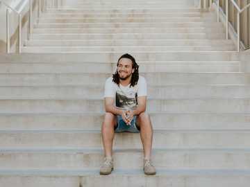 Man smiling on steps - smiling man sitting on staircase. University of Arkansas, Fayetteville, United States