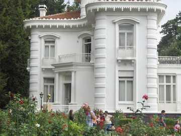 dom z ogrodem - biały dom z ogrodem kwiatowym