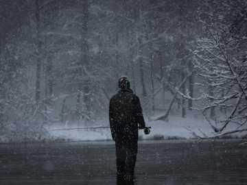 Fotografía en escala de grises del hombre pescando mientras nieva - Pesca de trucha Steelhead en el río Pere Marquette de Michigan con zancudas para pararse en las agu