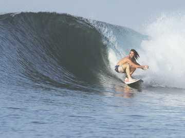 homme surf avec grosse vague - Surfeur accroupi en action. Sumbawa, Indonésie