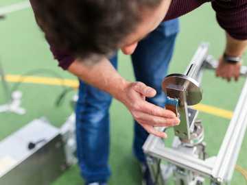 Inżynier sportowy testuje sprzęt do tenisa - osoba w czerwonej koszuli z długim rękawem z lupą.
