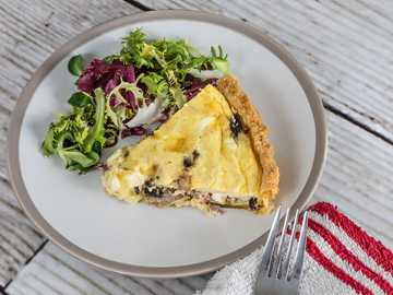 Quiche and Salad - sliced pie on white ceramic plate. New York, Texas, United States