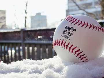 Baseball im Schnee - weißer und roter Baseball auf schwarzem Metallzaun während des Tages. Toronto, ON, Kanada