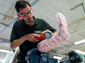 Inżynier technika ortotycznego wykonuje spersonalizowane nogi - mężczyzna w czarnej koszulce z okrągłym dekoltem i pomarańczowym i czarnym zabawkowym pistolete