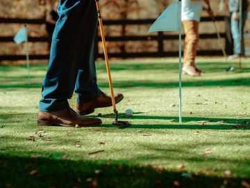 osoba w niebieskiej szacie trzyma kij golfowy - Stawianie na zielono z kijem golfowym i piłką na imprezie z trawnikiem. Cameron Park, Kalifornia,