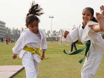 Jeunes filles pratiquant et enseignant les arts martiaux aux étudiants - 2 femmes en chemise à manches longues blanches debout sur le champ d'herbe verte pendant la jo