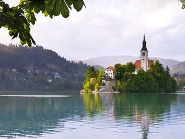 Island in the lake, with a chuch - white and brown concrete building near body of water during daytime. Bled, Slovenia