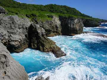 Pagat Caves - green cliff beside sea. Yigo, Yigo, United States