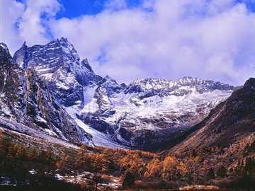 The color is not the PS effect. I use Kodak 100vs. - couple walks on landscape with snowy mountain background. 中国阿坝藏族羌族自治州理县毕
