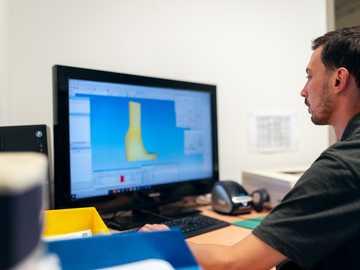 mężczyzna w czarnej koszulce siedzi przed komputerem - Mężczyzna inżynier technik ortotyczny projektuje spersonalizowaną obsadę nogi.