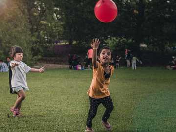 Des enfants heureux - deux filles jouant au ballon. Jardin botanique de Singapour, Singapour