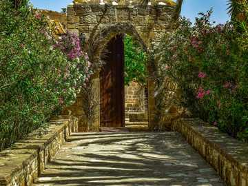 Monastery gate - stone path and flowers