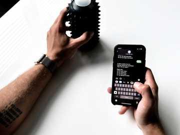 Teléfono en mano - Persona con dispositivo digital sony negro.