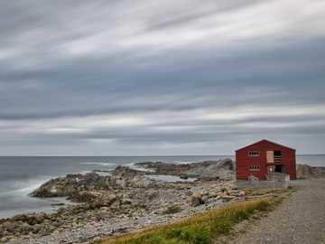 Chałupa rybacka - punkt miotły - czerwony drewniany dom w pobliżu morza w ciągu dnia.