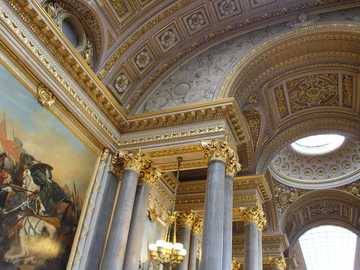 photo of building interior with painting - This was in one of the great halls at Versailles. The crown detail was amazing. Palace of Versailles
