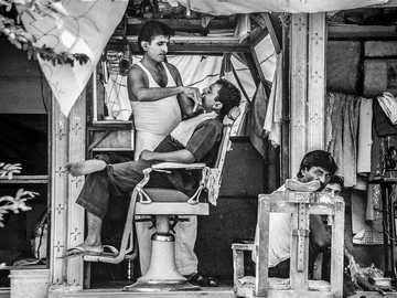monochromatyczny fryzjer uliczny - zdjęcie w skali szarości fryzjera przycinającego brodę mężczyzny.