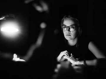 Pracować do późna - w skali szarości zdjęcie kobiety w okularach siedzącej przed stołem. Czerepowiec, Rosja