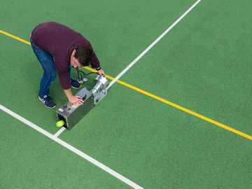 Męski inżynier sportowy testuje sprzęt do tenisa - mężczyzna w czerwonej koszuli i niebieskich dżinsach, grając w golfa.