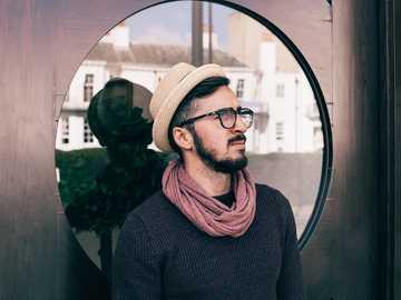 Hombre con ventana circular - Hombre vestido con anteojos y camisa negra, apoyado en la puerta de cristal mientras mira hacia arri