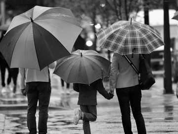 Deszczowe dni w Vancouver - fotografia w skali szarości przedstawiająca trzy osoby trzymające parasol. Vancouver, Kanada