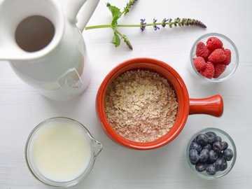 Healthy Breakfast - bowl of cereal near white pitcher.
