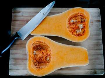 Butternut squash - stainless steel knife on brown wooden chopping board.