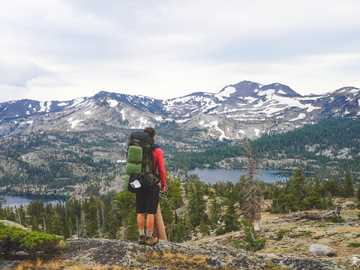 person standing on mountain wearing backpack - Stopping to appreciate the beauty of Desolation Wilderness near Lake Tahoe, CA. Desolation Wildernes