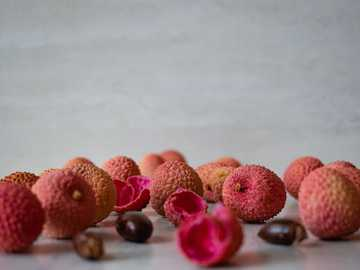 lychee berries with peel and pit - brown and pink round fruit on white table.