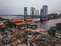 Demolição de Jacksonville Landing com vista da ponte - fotografia aérea de garra escavadeira amarela na loja de cinta de metal. Jacksonville, Flórida, EU