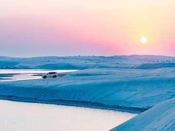 Zachód słońca w krajobrazie pustyni Doha - biały SUV na białym ośnieżonym polu obok zbiornika wodnego w ciągu dnia. Doha, Katar