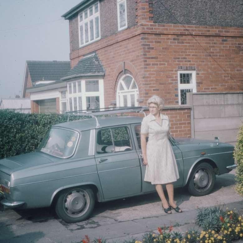 Jaren 70 120mm film dia foto - vrouw in witte jurk met lange mouwen staan naast groene auto overdag (6×6)