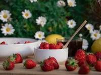 jahody a žluté květy v bílé keramické misce