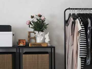 pink flowers in white vase on table - Capsule wardrobe in an open storage system. . United Kingdom