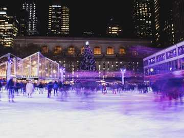 crowd on ice rink during night - Somewhere Between Living & Dreaming. Bryant Park, New York