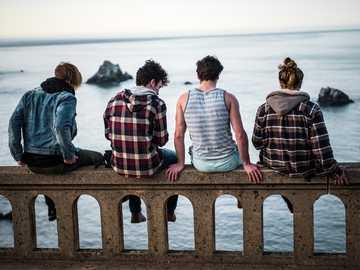 Życie na krawędzi - cztery osoby siedzące na ławce przed zbiornikiem wodnym. Bixby Creek Bridge, Monterey, Stany Zjedn