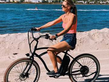 Riding a Tower Electric Bike along the beach. - woman in blue spaghetti strap top and blue denim shorts sitting on black commuter bike on on on on o