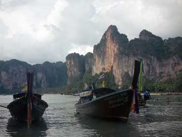 Longtail boats, Thailand - brown boat on body of water near brown rock formation during daytime. Krabi, Thailand