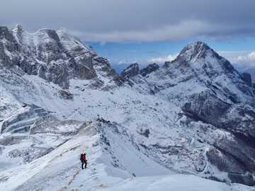 homme sur une montagne enneigée - Ascension de la crête du Monte Tambura en hiver, sur le fond Monte Cavallo et Pisanino, le plus hau