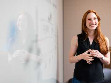 woman in blue tank top standing beside white wall - Female software engineer in meeting by whiteboard.